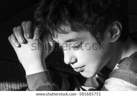 Young boy smiling peacefully as he says bedtime prayers, black and white, Christian religious concept