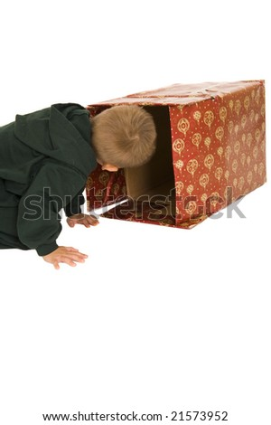 Young boy sneaking a peek in a Christmas box. Isolated on white.