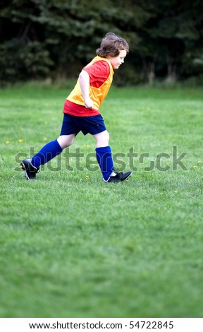 Young boy soccer player running on soccer field