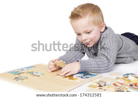 Young boy solving a puzzle. Isolated on white - stock photo