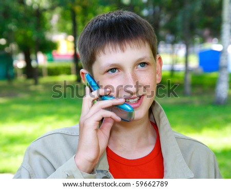 young boy speaks by phone outdoors - stock photo