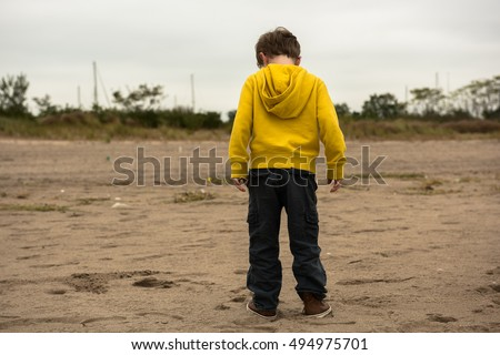 Young boy standing alone waiting on a New York City beach in the Fall