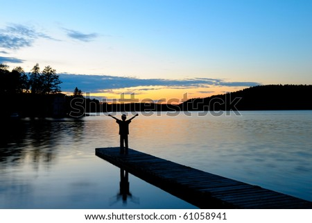 Young Boy Standing and waving on a Dock at Sunset - stock photo