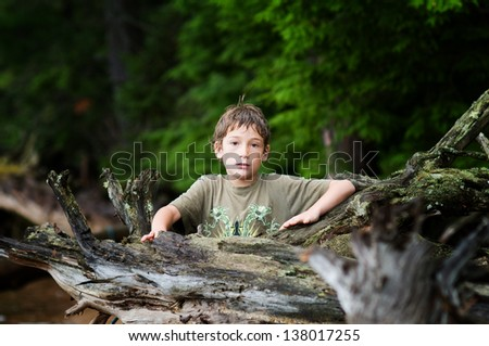 young boy standing by the large upturned root of a tree looking serious - stock photo