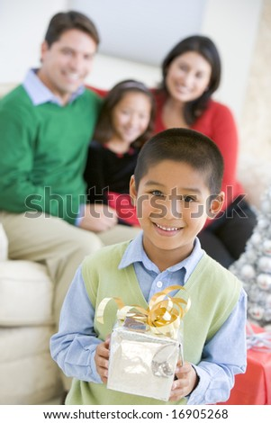 Young Boy Standing Holding Christmas Present,With His Parents And Sister In The Background - stock photo
