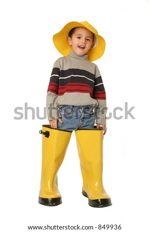 young boy standing in large yellow rain boots and a yellow rain hat isolated on white - stock photo