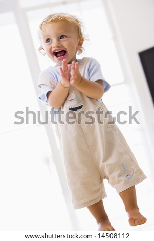 Young boy standing indoors applauding and smiling - stock photo