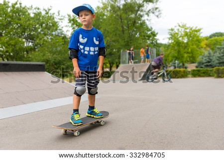 young boy standing on his skateboard at a skate park watching something in the distance with a serious expression - stock photo