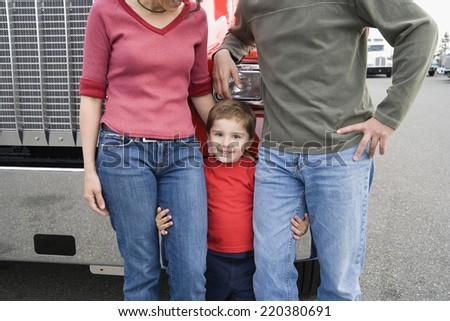 Young boy standing with his parents - stock photo