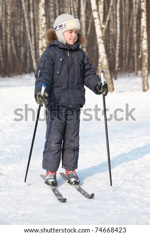 Young boy stands on cross-country skis and looking to side inside winter forest at sunny day - stock photo