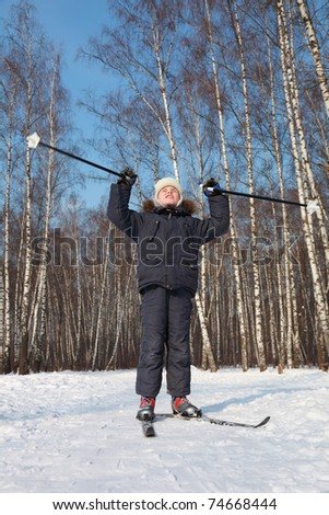 Young boy stands on cross-country skis, looks to sky and wave poles inside winter forest at sunny day - stock photo