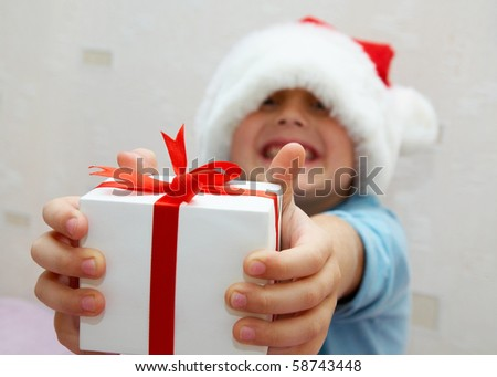 young boy stretches out a beautiful gift in hands