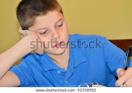 Young boy struggles with boredom while studying - stock photo