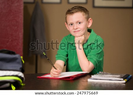 Young boy studying and doing school homework at table. - stock photo