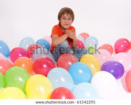 Young boy surrounded by colourful balloons - stock photo