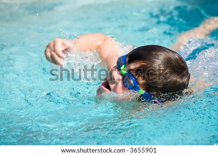young boy swimming in pool taking a breath of air