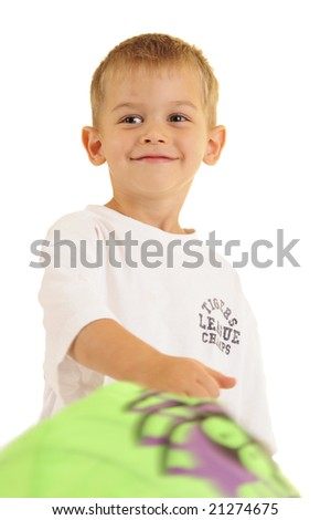 Young boy swinging bag and smirking at camera. White background.