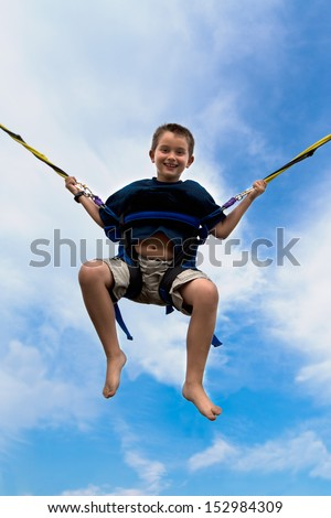 Young boy swinging high in the air against a cloudy blue summer sky in a harness attached to cables or ropes with a beaming smile of enjoyment - stock photo