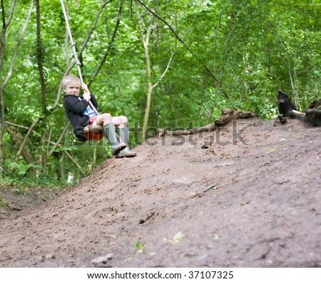 Young boy swinging on a rope swing in the woods