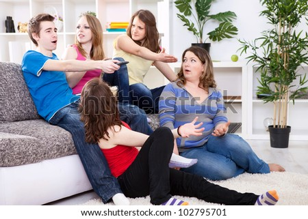Young boy  switches the channel on TV, unsatisfied girls watching  him - stock photo