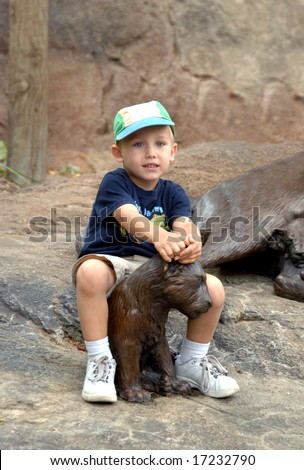 Young boy takes a ride on a lion cub sculpture.
