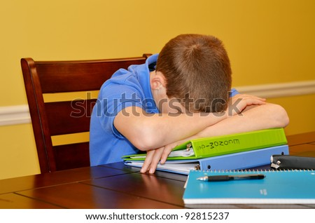 Young Boy taking a nap while he should be studying - stock photo