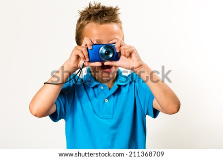 Young boy taking a photo. Studio shot with white background.