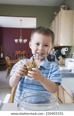 Young boy taking cookie from cookie jar - stock photo