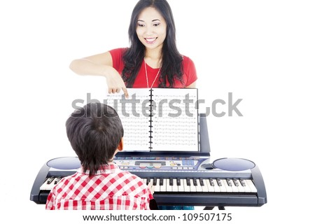 Young boy taking piano lessons at home with his tutor - stock photo