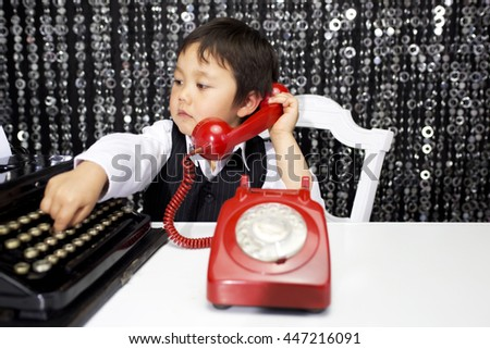 young boy talks on a red telephone - stock photo