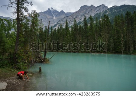 Young boy  tests the waters of the Robson River along the Berg Lake Trail near Kinney Lake. - stock photo