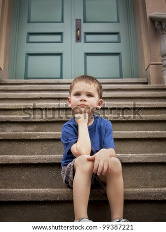 Young boy thinking and contemplating on the front steps of home or school - stock photo
