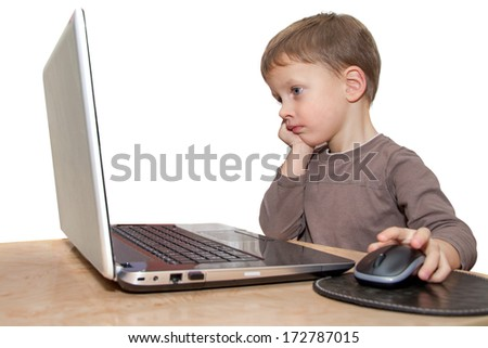 young boy thinking in front of laptop - stock photo