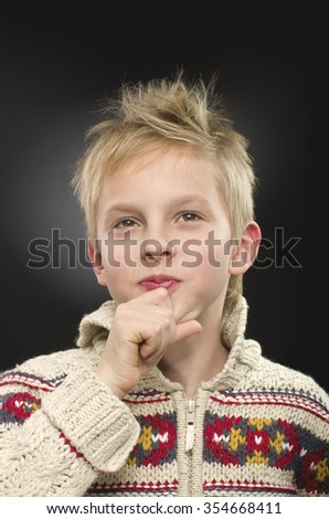 Young boy thinking, wondering on black background. - stock photo