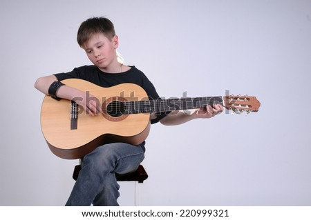 Young boy thoughtfully playing the guitar