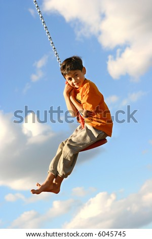 Young boy thrill on the chain swing against blue sky.