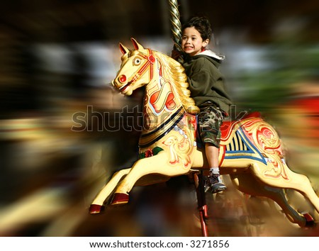 Young boy thrilled on the carousel ride, showing lots of movement.