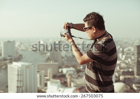 young boy tourist taking photos on the top of deserted building in Bangkok at Thailand