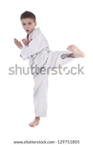 Young boy training kick isolated on white background - stock photo