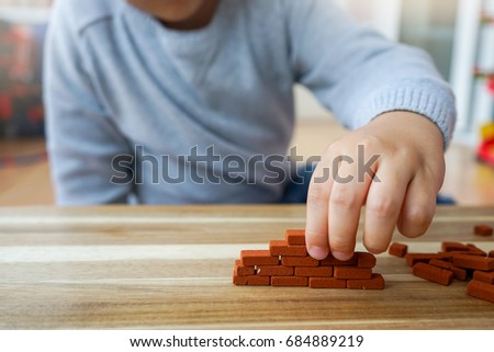 Young boy try to building a brick wall with miniature in playroom at home, Concept for Education or IQ learning