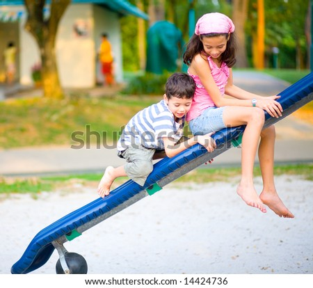 Young boy trying his best to climb on the slide in playground as  sister watches. - stock photo