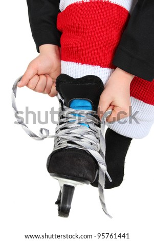 Young boy tying his Ice Skates in hockey uniform - stock photo