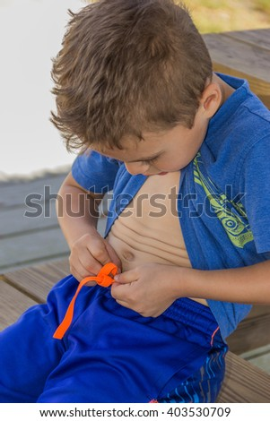 Young boy tying his shorts string