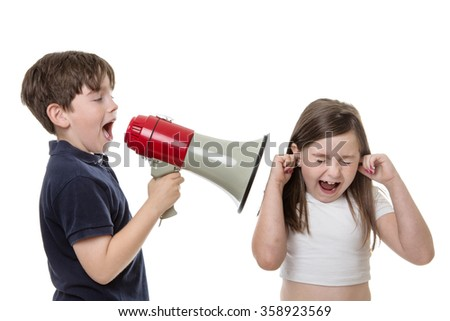 Young boy uses a bull horn to speak loudly into a girls ear - stock photo