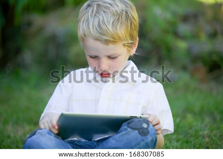 Young boy using a computer tablet. - stock photo