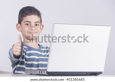 Young boy using a laptop computer (e learning concept). Toned image with selective focus - stock photo