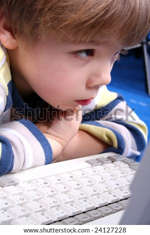 Young boy using a laptop in home - stock photo