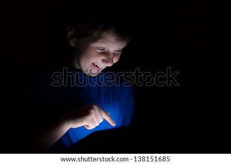 young boy using an electronic tablet device with finger pointing. Light coming from the tablet - stock photo
