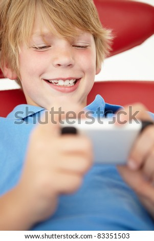 Young boy using cellphone - stock photo
