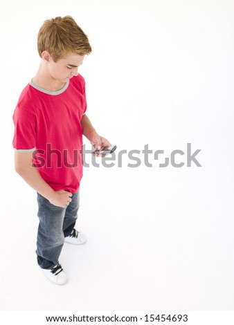 Young boy using cellular phone - stock photo